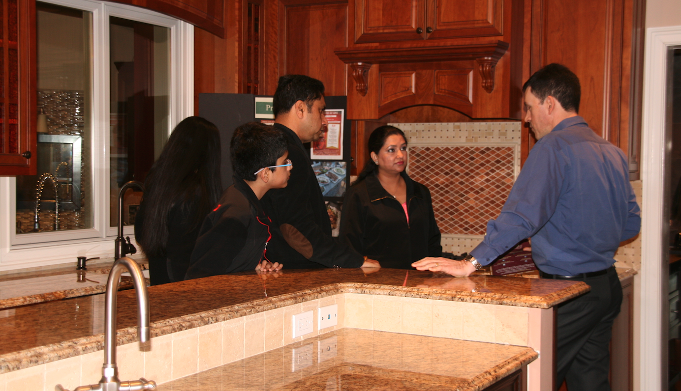 Alure Home Improvements salesperson in the showroom with customers