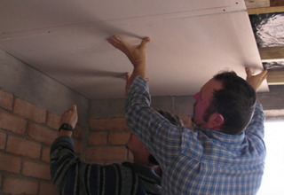 Workers install drywall in ceiling