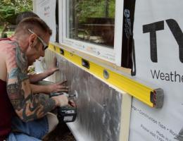 Workers leveling and fastening a rigid foam panel