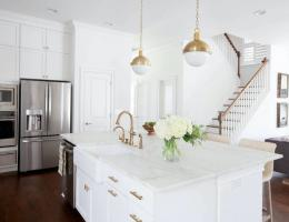 white kitchen with island, pendant lights, and cabinetry