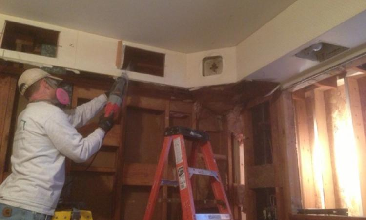 Worker with respirator sawing drywall