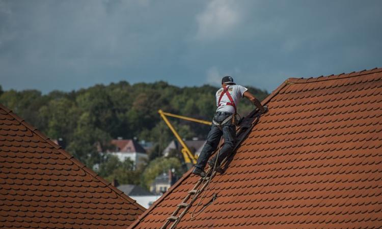 Roofer with harness on rooftop