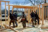 crew raising a frame on a home for remodel