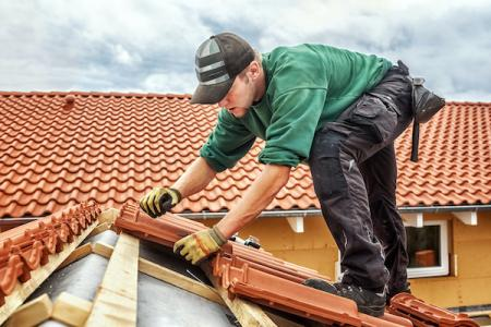 contractor working on a roof for a roofing job with brick